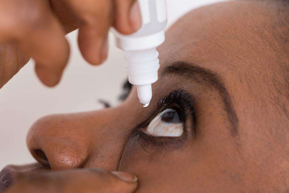 Closeup of a Woman Placing Eye Drops in Her Eye